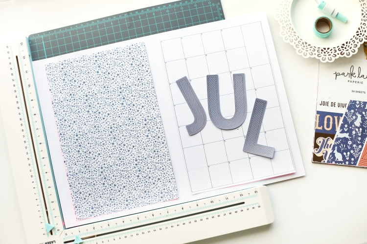 DIY Wall Calendar featuring the We R Memory Keepers Foil Quill and the Park Lane Je Ne Sais Quoi 12x12 Paper Pad available at Joann Stores. Project created by Eva Pizarro for We R Memory Keepers.